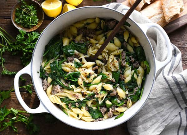Overhead shot of pasta with sausage and spinach in a white dutch oven