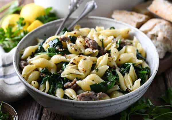 Horizontal shot of a bowl of skillet penne with sausage and spinach