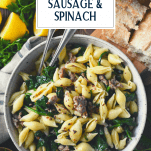 Overhead shot of a bowl of pasta with sausage and spinach with text title overlay