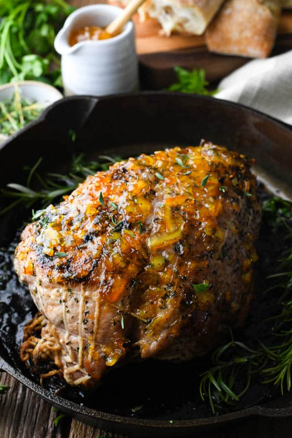 Side shot of the best pork sirloin roast recipe in a cast iron skillet with fresh herbs