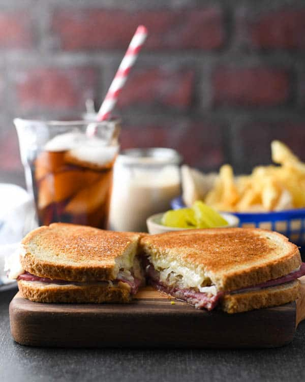 The best reuben sandwich recipe on a wooden cutting board with soda and chips in the background