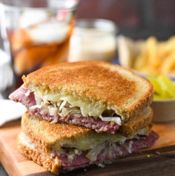 Two halves of a reuben sandwich stacked on a wooden cutting board