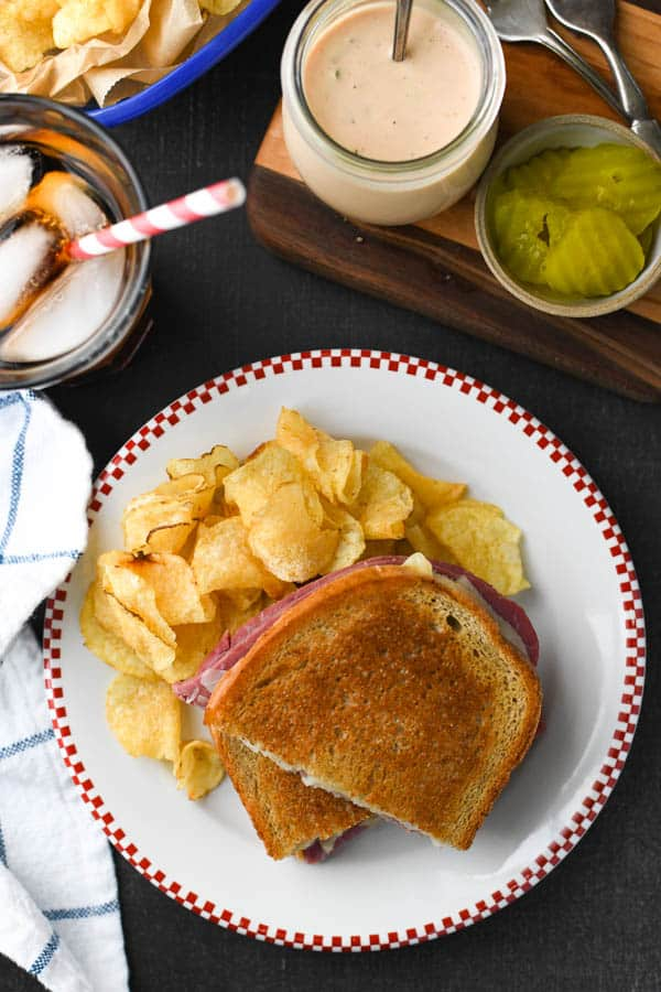 Overhead shot of a homemade reuben sandwich on a plate with potato chips and a side of pickles