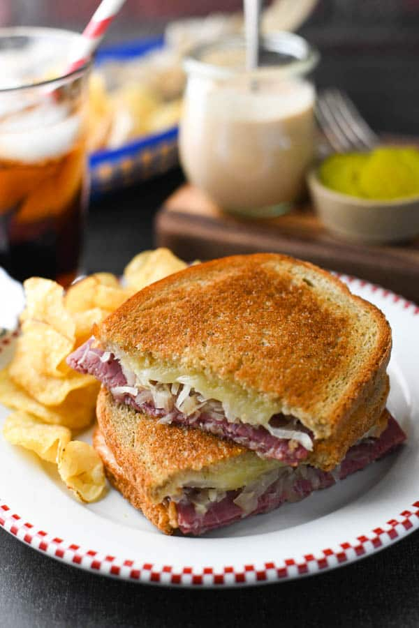 Stacked classic reuben sandwich on a plate with potato chips