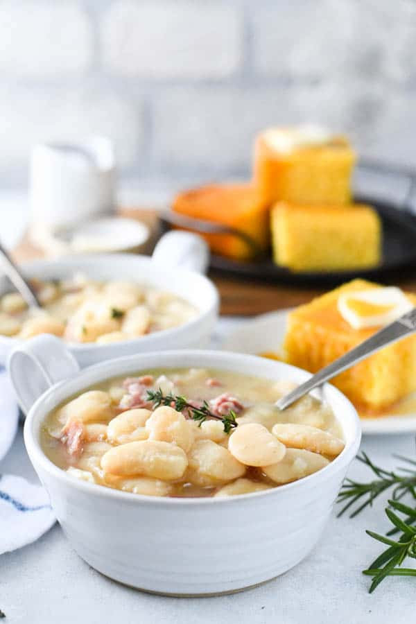 Front shot of butter beans in a white bowl with cornbread in the background