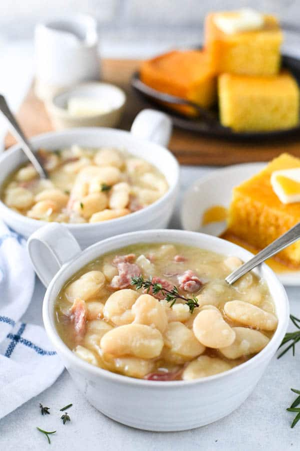 Side shot of two bowls of butter beans with ham and cornbread