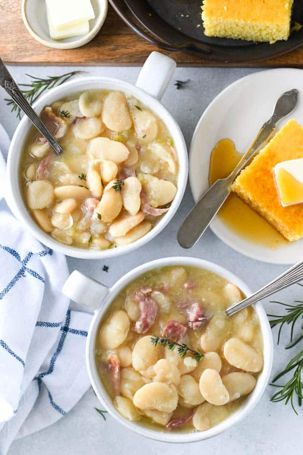 Two bowls of large lima beans cooked with ham hocks and served with cornbread