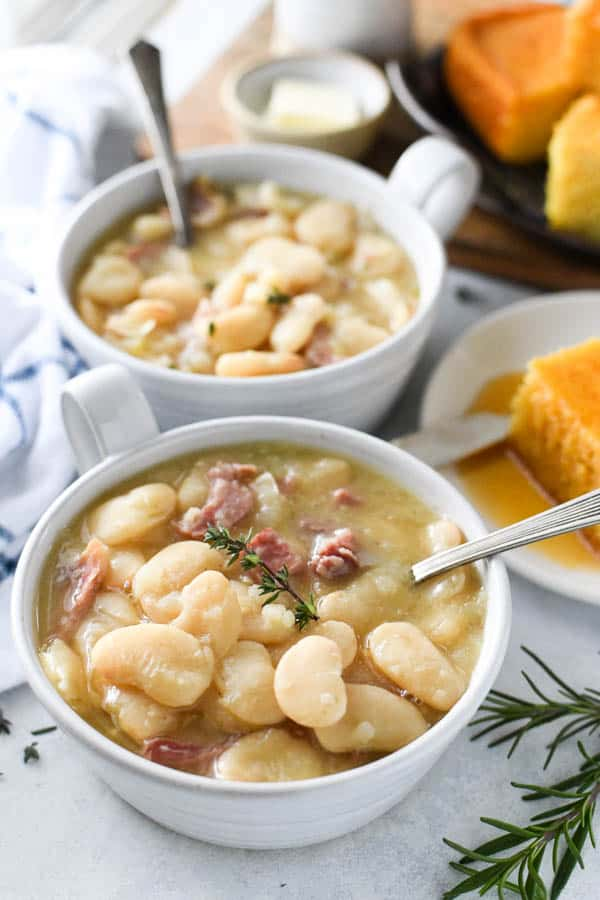 Front shot of two white bowls full of southern lima beans with ham