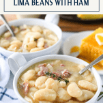 Front shot of two bowls of lima beans with ham and cornbread and text title box at top