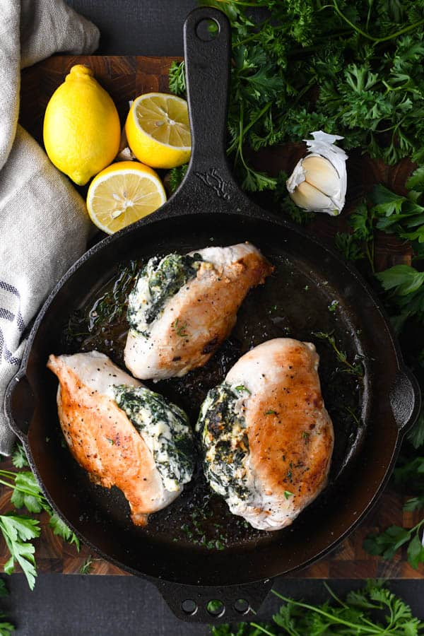 Overhead shot of spinach and cheese stuffed chicken in a skillet