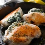Front shot of spinach stuffed chicken breasts in a cast iron skillet
