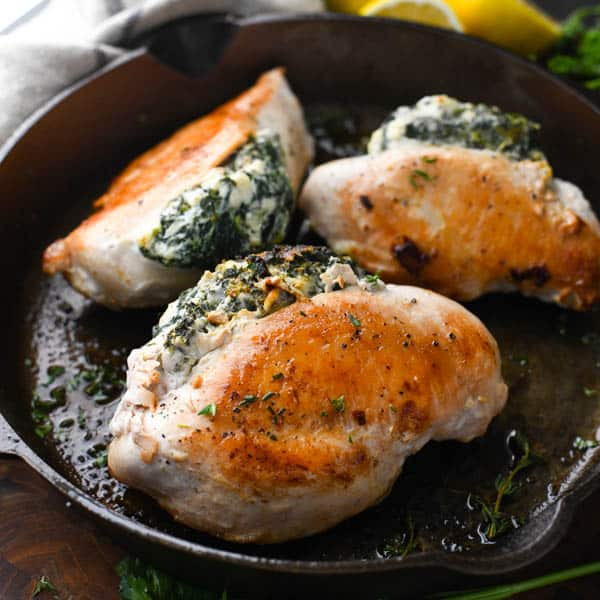 Square image of feta and spinach stuffed chicken in a cast iron skillet
