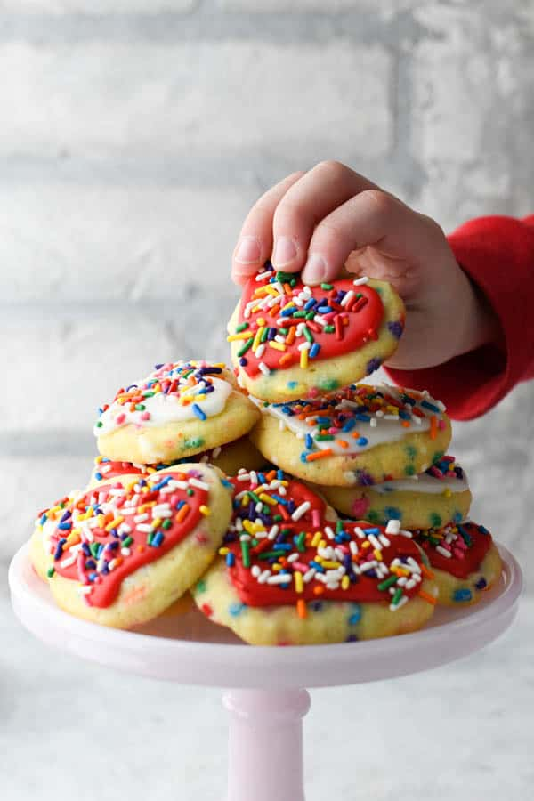 Kids hand picking up a heart shaped sugar cookie with rainbow sprinkles for Valentine's Day