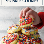 Child picking up sprinkle cookies with text title box at top