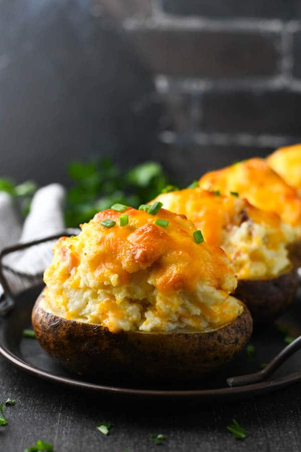 Front shot of make ahead twice baked potatoes in front of a dark brick wall