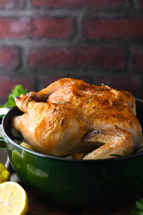Side shot of crispy roast chicken in a dutch oven
