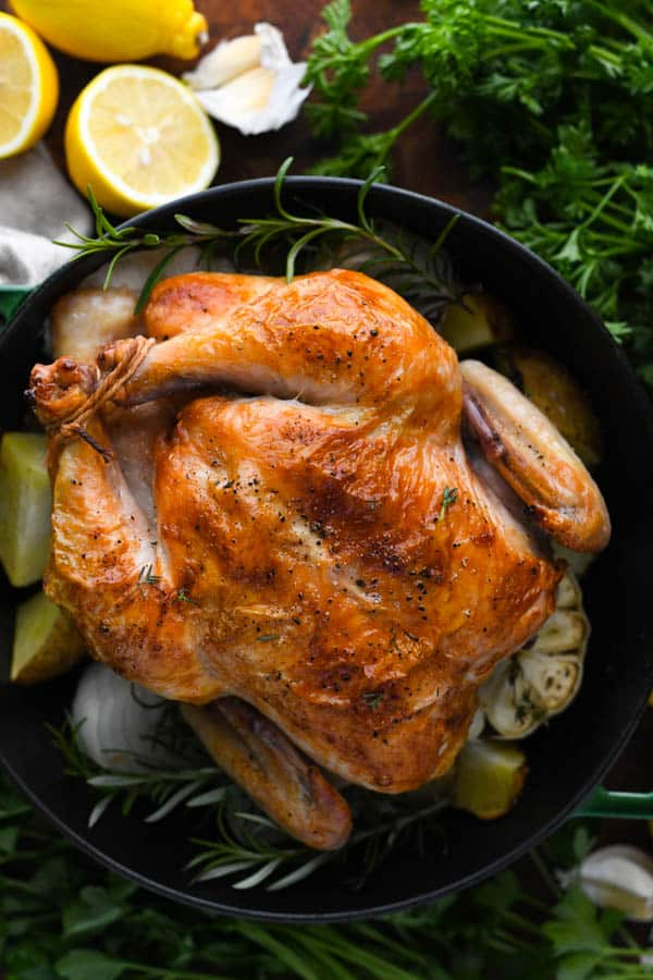 Overhead shot of whole roasted chicken in a Dutch oven