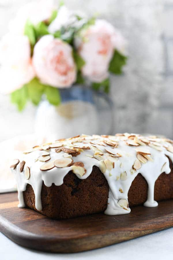 Glaze and sliced almonds on top of a loaf of cherry quick bread.