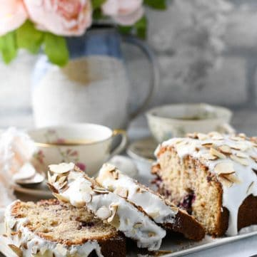 Side shot of a cherry almond loaf cake sliced on a white tray with flowers in the background.