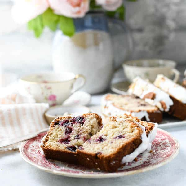 Square image of two slices of classic cherry bread on a plate in front of pink flowers