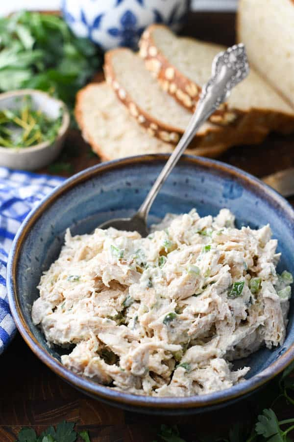 Close up front shot of the best chicken salad recipe in a blue serving bowl with homemade bread in the background