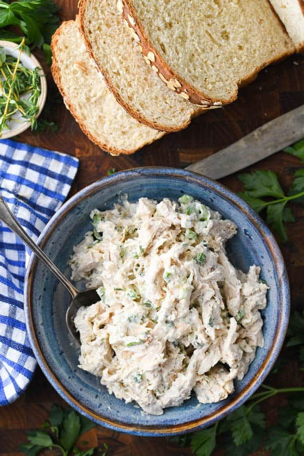 Overhead shot of a bowl of the best recipe for chicken salad with sliced loaf of bread nearby