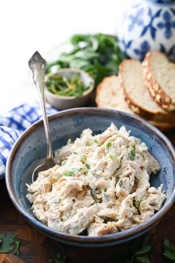 Side shot of shredded chicken salad recipe in a blue bowl with a silver serving spoon