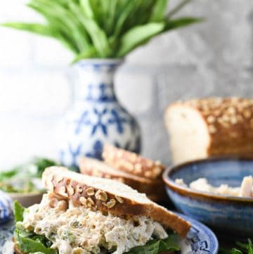 Easy rotisserie chicken salad recipe served on a sandwich with lettuce and yellow tulips in the background