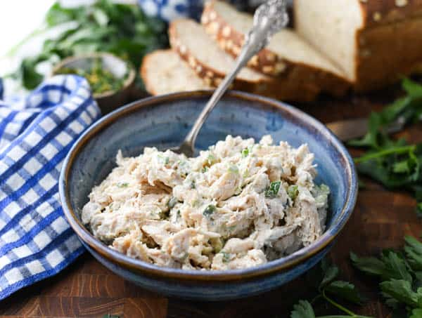 Horizontal shot of the best chicken salad recipe in a blue bowl with a serving spoon