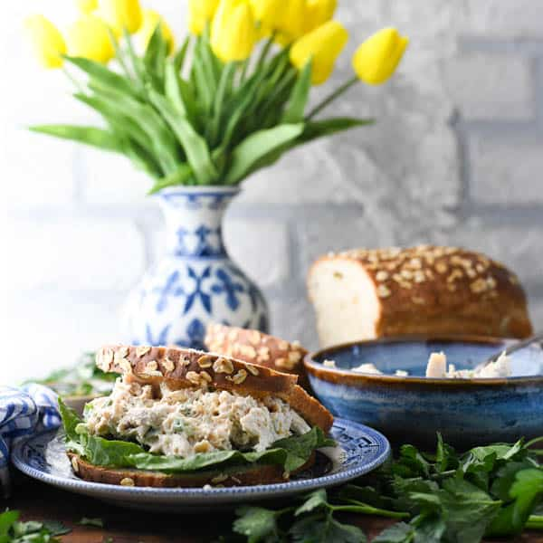 Square image of a homemade chicken salad sandwich on a blue and white plate