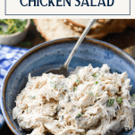 Close up shot of a blue bowl full of the best chicken salad recipe with text title box at top