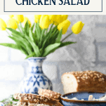 Front shot of the best chicken salad recipe served on a sandwich with text title box at top