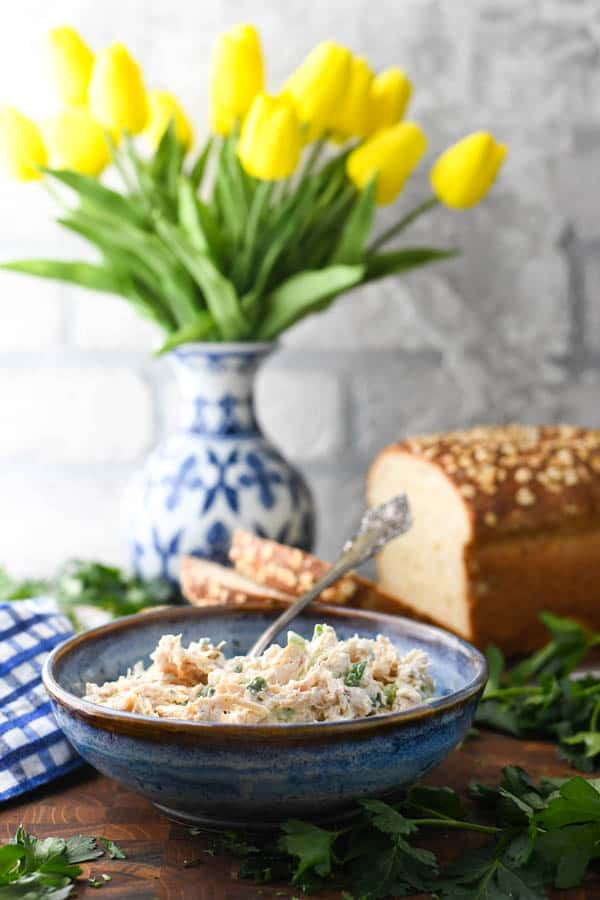 Front shot of an easy chicken salad recipe served in a blue bowl on a wooden table