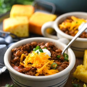 Front shot of two bowls of chili with cheese and other toppings