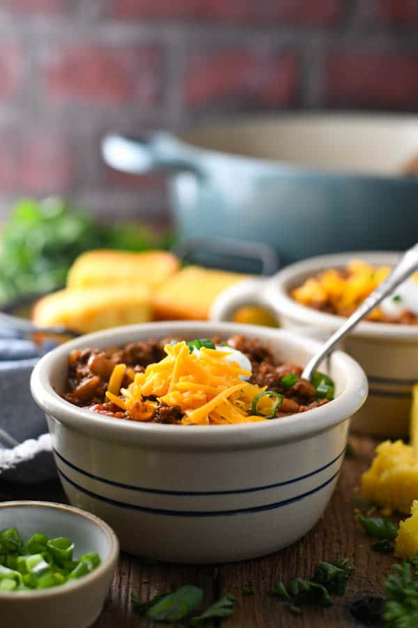 Front shot of two bowls of beef chili on a table with cornbread