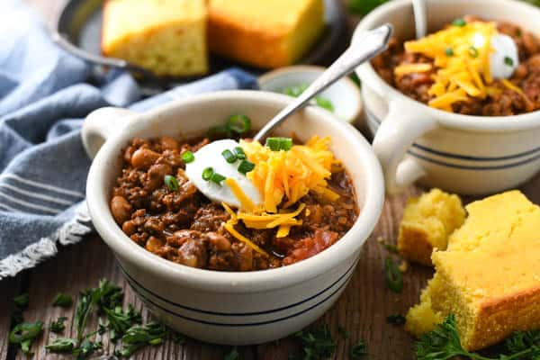 Horizontal shot of a bowl of the best beef chili recipe served with a side of cornbread