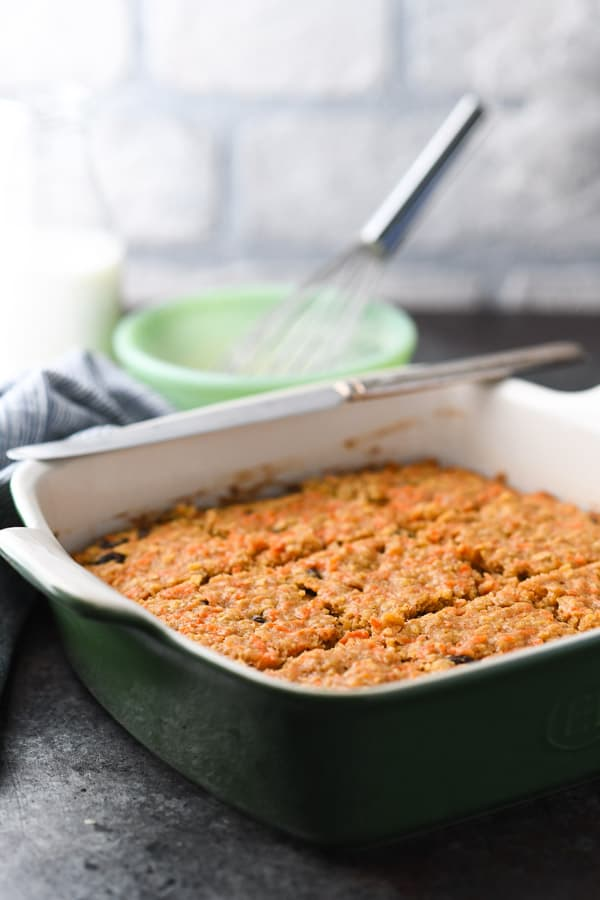Baked oatmeal bars in a green dish cut into squares.