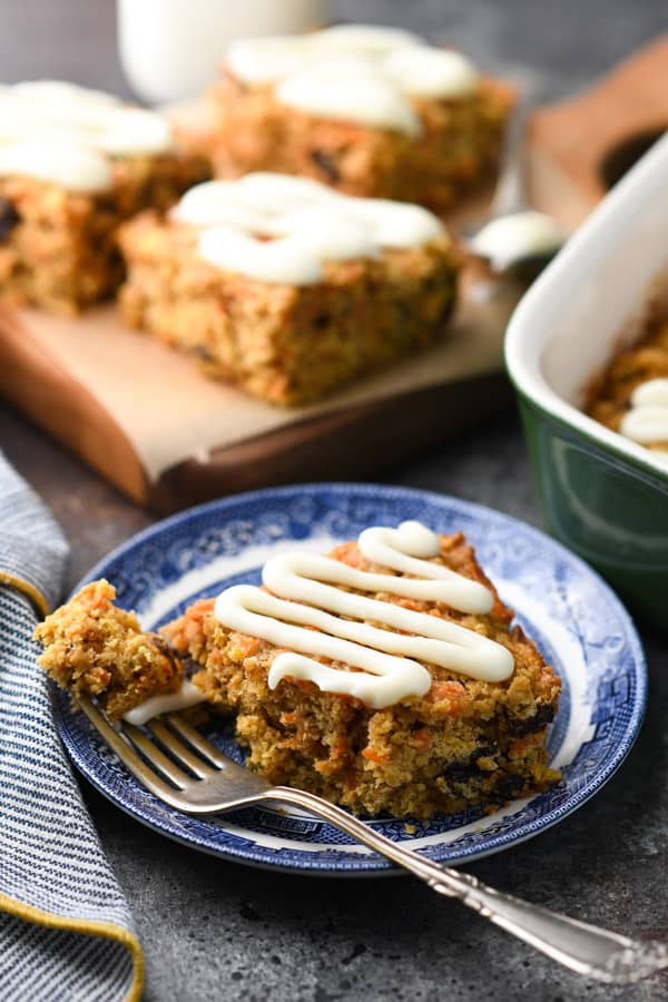 Close up side shot of homemade carrot cake baked oatmeal bars with a cream cheese glaze.