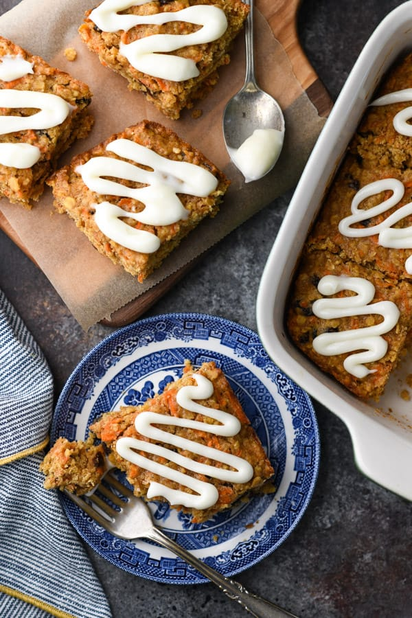Overhead shot of baked oatmeal bars on a table drizzled with cream cheese glaze.