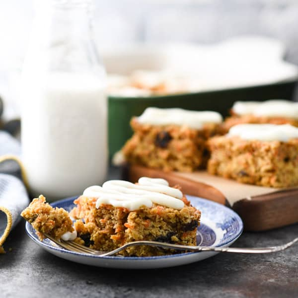 Square shot of carrot oatmeal bars on a plate and cutting board with milk