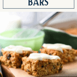 Side shot of carrot oatmeal bars on a cutting board with text title box at top