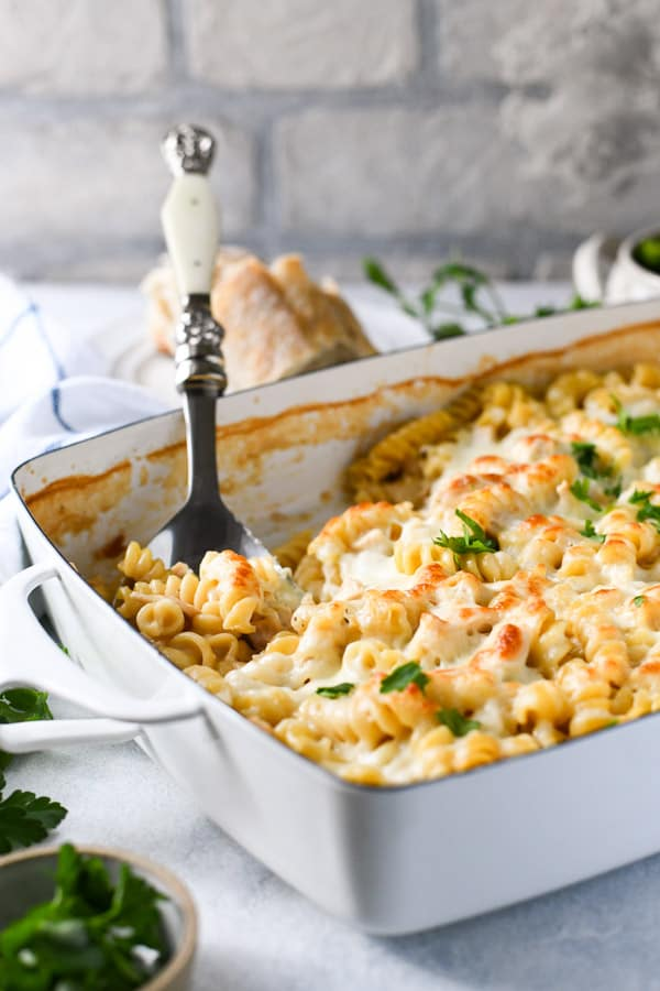 Cheesy chicken alfredo casserole recipe in a white baking dish on a white table