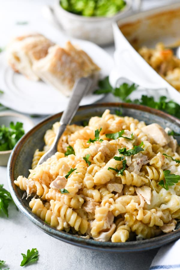 Easy chicken alfredo casserole served in a blue bowl with cheese on top