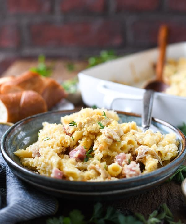 Front shot of a bowl of chicken cordon bleu casserole in front of a brick wall