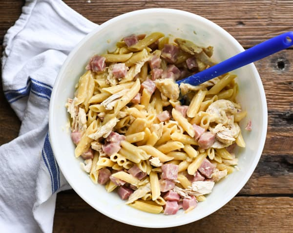 Process shot showing how to assemble leftover ham and chicken casserole with noodles