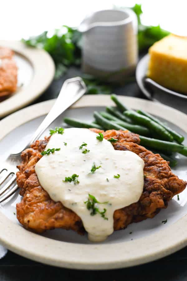 Side shot of chicken fried steak with gravy on a plate with green beans and cornbread