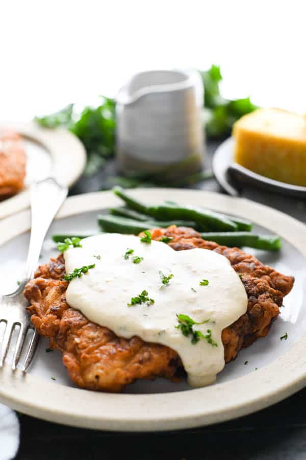 Front shot of a plate of the best chicken fried steak recipe served with green beans
