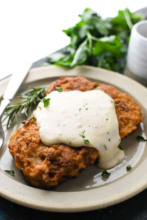 A piece of Southern chicken fried steak with gravy on a plate with fresh herb garnish