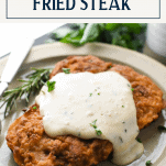 Easy chicken fried steak on a plate with gravy and fresh herbs and text title box at top