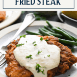 The best chicken fried steak recipe on a plate with text title box at top